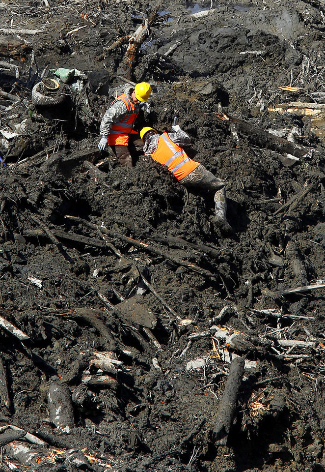 Photo - Rescuers work through deep mud at the site of a fatal mudslide on Tuesday, April 1, 2014, near Oso, Wash. The March 22 mudslide destroyed a rural mountainside community northeast of Seattle. (AP Photo/The Herald, Mark Mulligan) MANDATORY CREDIT.