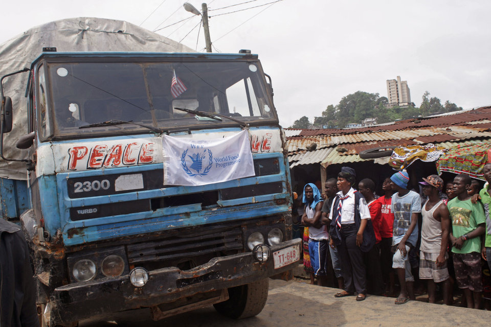 Photo - People gather, right, around a truck with food stuff from the World Food Programme, WFP,  before they enter the West Point area that have been hardest hit by the Ebola virus spreading in Monrovia, Liberia, Monday, Aug. 25, 2014.  A Liberian doctor who was among three Africans to receive an experimental Ebola drug has died, the country's information minister said Monday. (AP Photo/Abbas Dulleh)