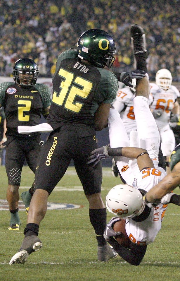 Photo - OSU's Damian Davis is brought down by Oregon's Jairus Byrd during the Holiday Bowl college football between Oklahoma State and Oregon at Qualcomm Stadium in San Diego, Tuesday, Dec. 30, 2008.  PHOTO BY BRYAN TERRY, THE OKLAHOMAN.
