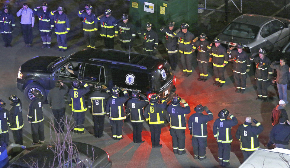 Photo - In this photo made Wednesday night, March 26, 2014, firefighters salute the medical examiner's truck carrying the body of one of two firefighters killed when a fire driven by strong winds whipped through a four-story apartment building in Boston and trapped them in the basement. (AP Photo/Boston Herald, Matt West) BOSTON GLOBE OUT. METRO BOSTON NEWSPAPER OUT. MAGS OUT. ONLINE OUT.