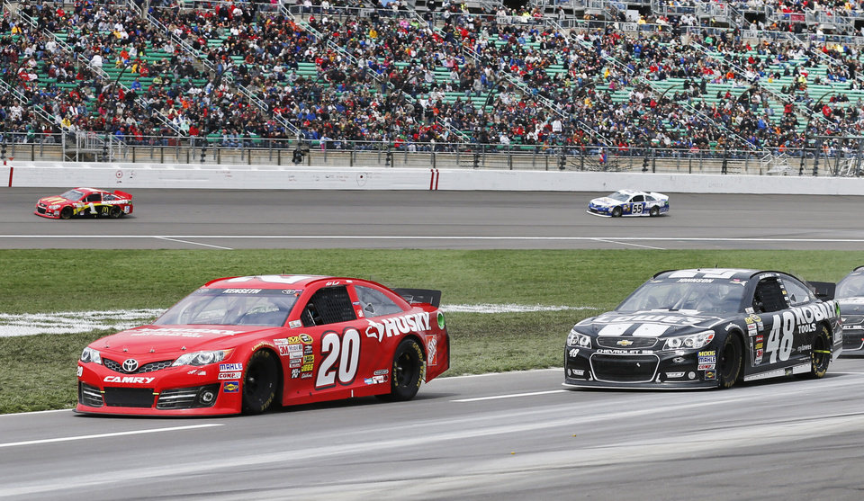 Photo - Matt Kenseth (20) and Jimmie Johnson (48) drive down pit row during a NASCAR Sprint Cup series auto race at Kansas Speedway in Kansas City, Kan., Sunday, April 21, 2013. (AP Photo/Orlin Wagner)
