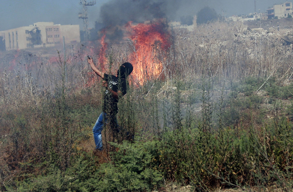 Photo - A Palestinian protester throws an empty tear gas canister towards Israeli troops, following a protest against the war in the Gaza Strip, during clashes near the West Bank town of Tulkarem on Friday, Aug. 1, 2014. A Palestinian man was shot and later died during clashes with Israeli troops near Tulkarem, Palestinian security sources said. (AP Photo/Mohammed Ballas)