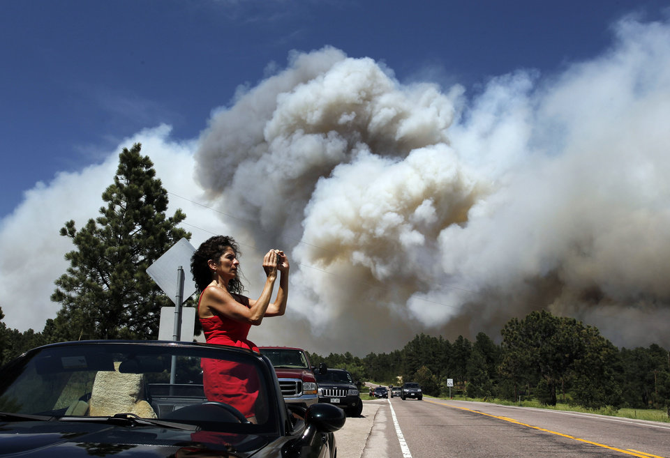 Photo - Colorado Springs resident Yolette Baca takes a photo of the wildfire in the Black Forest area north of Colorado Springs, Colo., on Wednesday, June 12, 2013. The number of houses destroyed by the Black Forest fire could grow to around 100, and authorities fear it's possible that some people who stayed behind might have died. (AP Photo/Brennan Linsley)