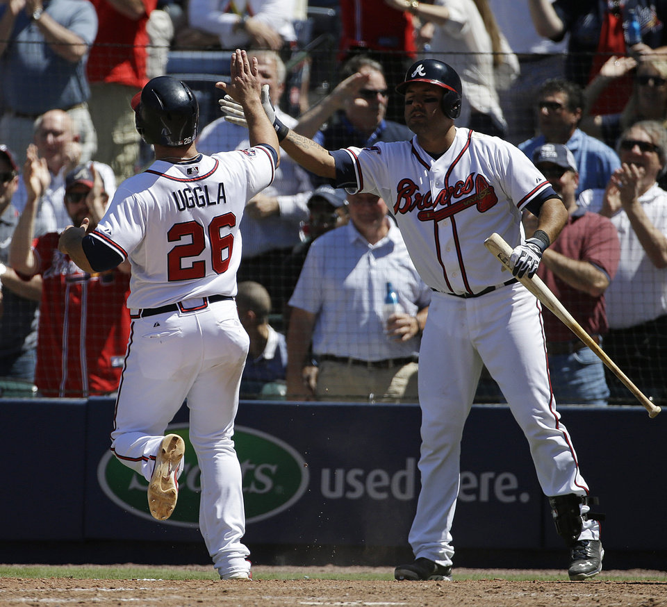 Photo - Atlanta Braves' Dan Uggla, left, high-fives teammate Gerald Laird after Uggla scored off a double by Evan Gattis in the eighth inning of a baseball game against the Miami Marlins, Wednesday, April 23, 2014, in Atlanta. The Braves won 3-1. (AP Photo/David Goldman)