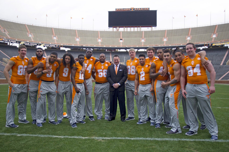 Photo - University of Tennessee NCAA college football coach Butch Jones, center, poses with his signing class' midterm enrollees on Wednesday, Feb. 5, 2014, in Knoxville, Tenn. The players are, from left to right: Daniel Helm, Neiko Creamer, Josh Malone, Von Pearson, Emmanuel Moseley, Dontavius Blair, Owen Williams, Ethan Wolf, D'Andre Payne, Coleman Thomas, Dimarya Mixon, Jalen Hurd, Jakob Johnson, and Ray Raulerson. (AP Photo/Knoxville News Sentinel, Saul Young)