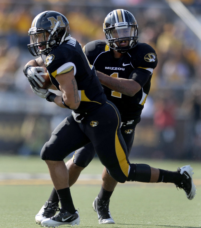 Photo - Missouri quarterback James Franklin, right, hands off to running back Kendial Lawrence as Lawrence runs for an 18-yard touchdown during the first half of an NCAA college football game against Oklahoma State Saturday, Oct. 22, 2011, in Columbia, Mo. (AP Photo/L.G. Patterson)