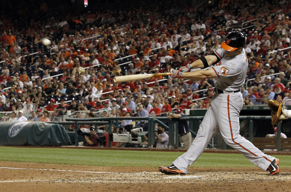 Photo - Baltimore Orioles' Chris Davis hits a two-run homer during the 11th inning of an interleague baseball game against the Washington Nationals at Nationals Park, Monday, July 7, 2014, in Washington. The Orioles won 8-2, in 11 innings. (AP Photo/Alex Brandon)
