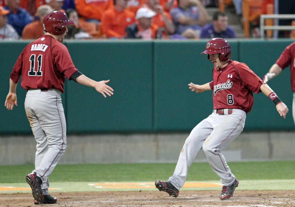 Photo - South Carolina's Marcus Mooney, right, celebrates with Zack Madden after they scored the winning runs in the ninth inning to defeat Clemson 5-3 in an NCAA college baseball game on Sunday, March 2, 2014, in Clemson, S.C. (AP Photo/Anderson Independent-Mail, Mark Crammer) GREENVILLE NEWS OUT; SENECA JOURNAL OUT