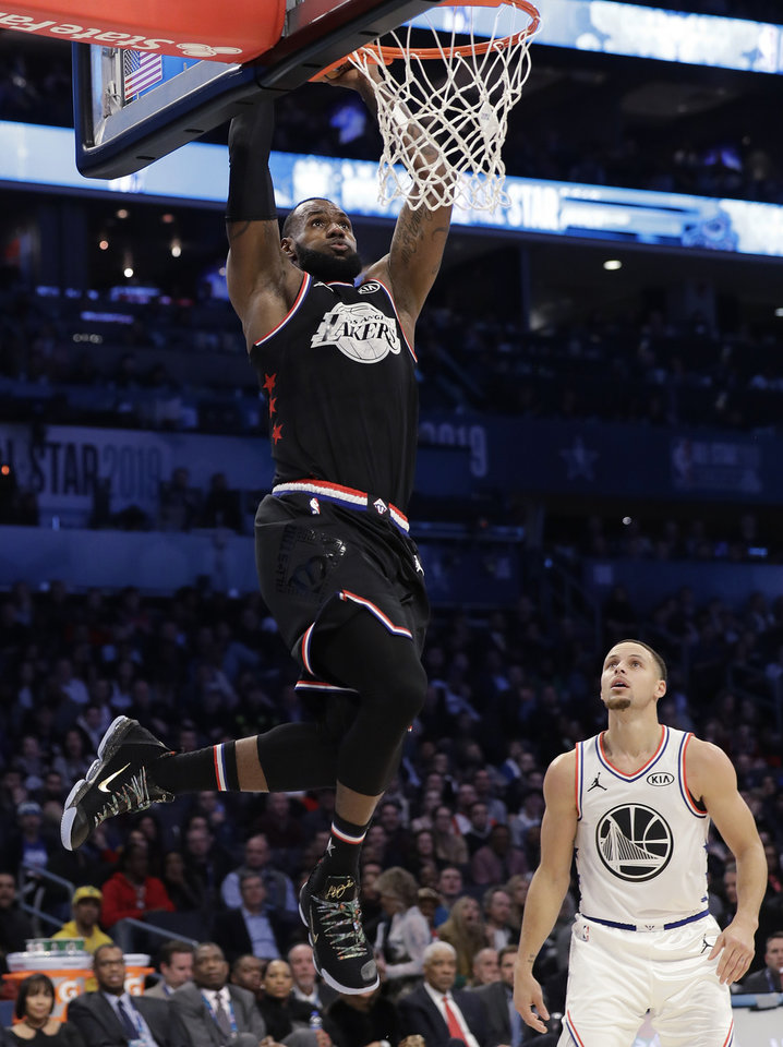 Photo - Team LeBron's LeBron James, of the Cleveland Cavaliers, dunks against Team Giannis' Stephen Curry, of the Milwaukee Bucks during the second half of an NBA All-Star basketball game, Sunday, Feb. 17, 2019, in Charlotte, N.C. The Team LeBron won 178-164. (AP Photo/Chuck Burton)