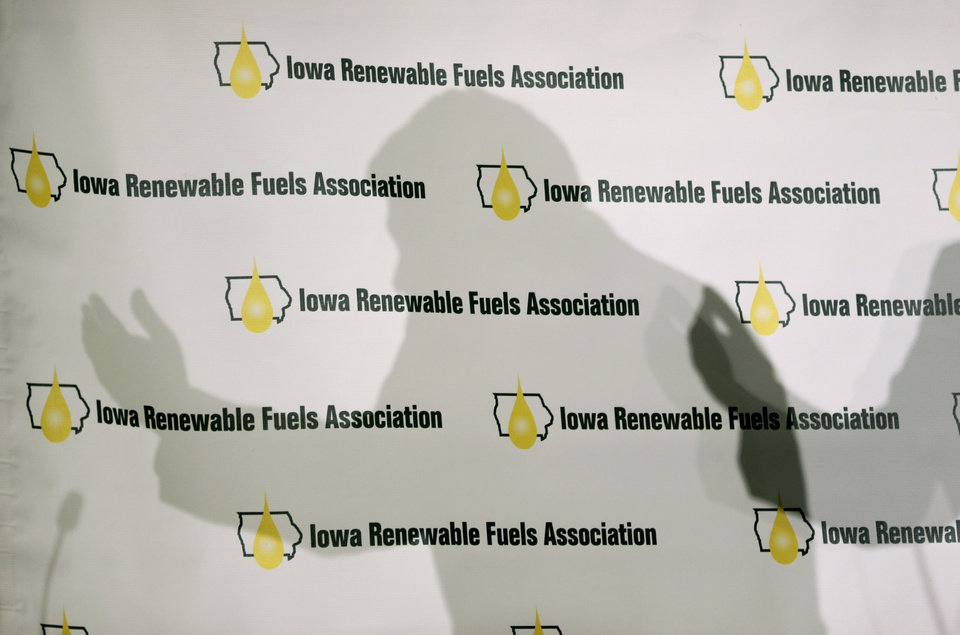 Photo - Iowa Gov. Terry Branstad casts a shadow on a backdrop as he speaks during the Iowa Renewable Fuels Association Summit, Tuesday, Jan. 28, 2014, in Altoona, Iowa. Branstad says he feels momentum is with Iowa and other farm states pushing the EPA to reverse a plan to cut the amount of biofuels blended into gasoline this year. (AP Photo/Charlie Neibergall)