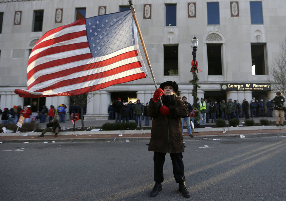 Protester Paula Merwin, of Leslie, Mich., stands with an American flag Tuesday outside the George W. Romney State Building, where Gov. Rick Snyder has an office, in Lansing, Mich. AP Photo