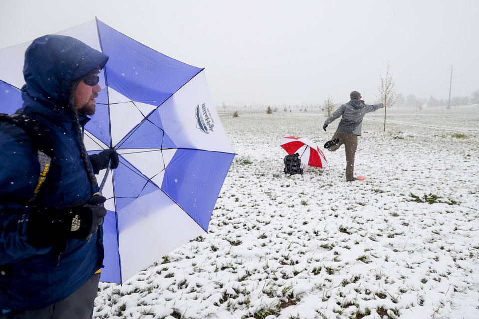 Photo - Mitch Sonderfan shields himself from the snow and wind with an umbrella as Pat Blazek throws a disc golf while competing in a tournament Sunday, May 11, 2014, at Aggie Greens in Fort Collins, Colorado. Snow is expected to fall through Monday, with highs reaching the sixties later this week. (AP Photo/The Coloradoan, Erin Hull)