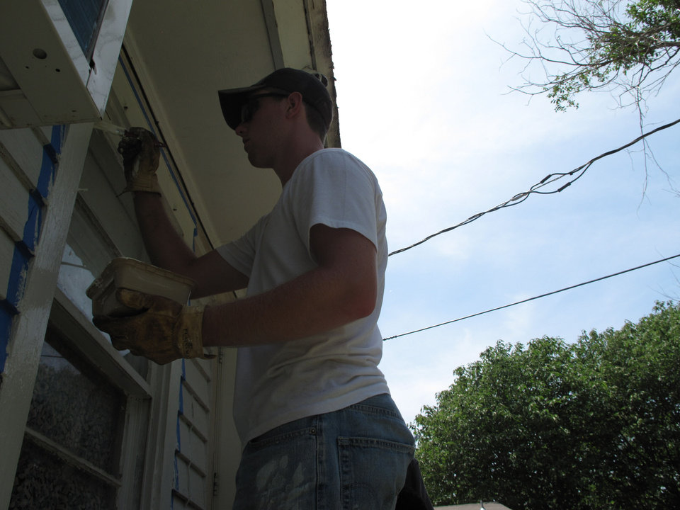 Photo - Dustin Preston, 18, with Main Street Baptist Church in Greenfield, Mo., paints an Edmond home Monday as part of North Church's Love OKC Student Conference. Photo by Carla Hinton, The Oklahoman