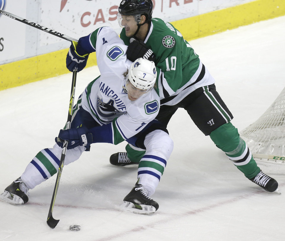 Photo - Vancouver Canucks left wing David Booth (7) and Dallas Stars center Shawn Horcoff (10) skate for the puck during the second period of an NHL hockey game Thursday, March 6, 2014, in Dallas. (AP Photo/LM Otero)