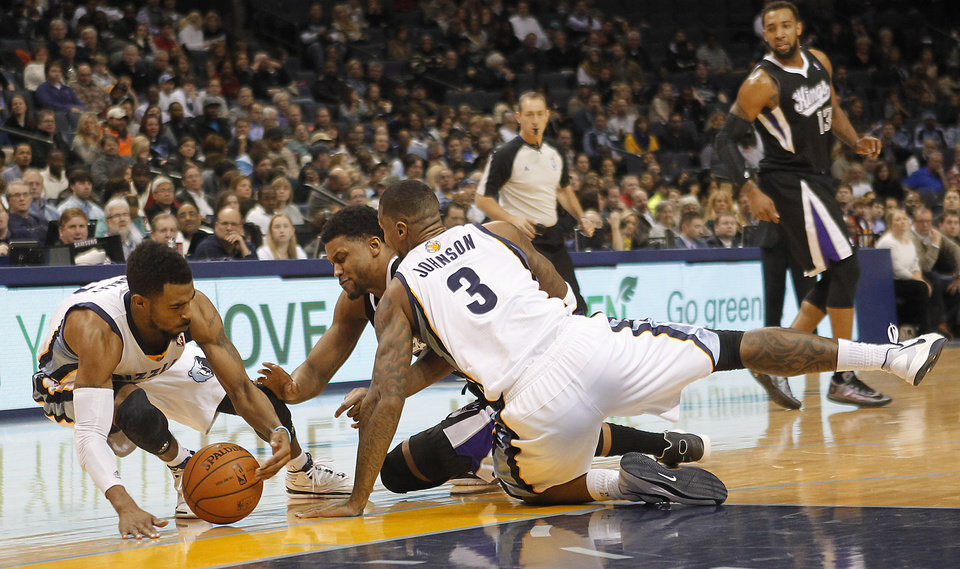 Photo - Memphis Grizzlies guard Mike Conley, left, and forward James Johnson (3) fight for a loose ball with Sacramento Kings forward Rudy Gay, center, in the first half of an NBA basketball game on Friday, Jan. 17, 2014, in Memphis, Tenn. (AP Photo/Lance Murphey)