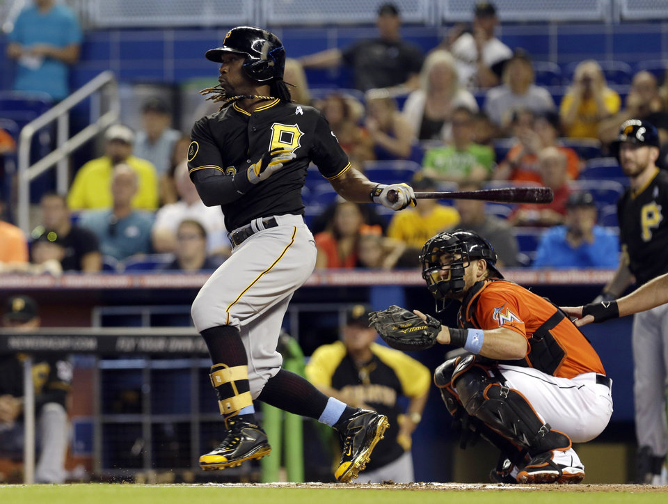 Photo - Pittsburgh Pirates' Andrew McCutchen, left, follows through on a base hit against the Miami Marlins in the first inning of a baseball game in Miami, Sunday, June 15, 2014. (AP Photo/Alan Diaz)
