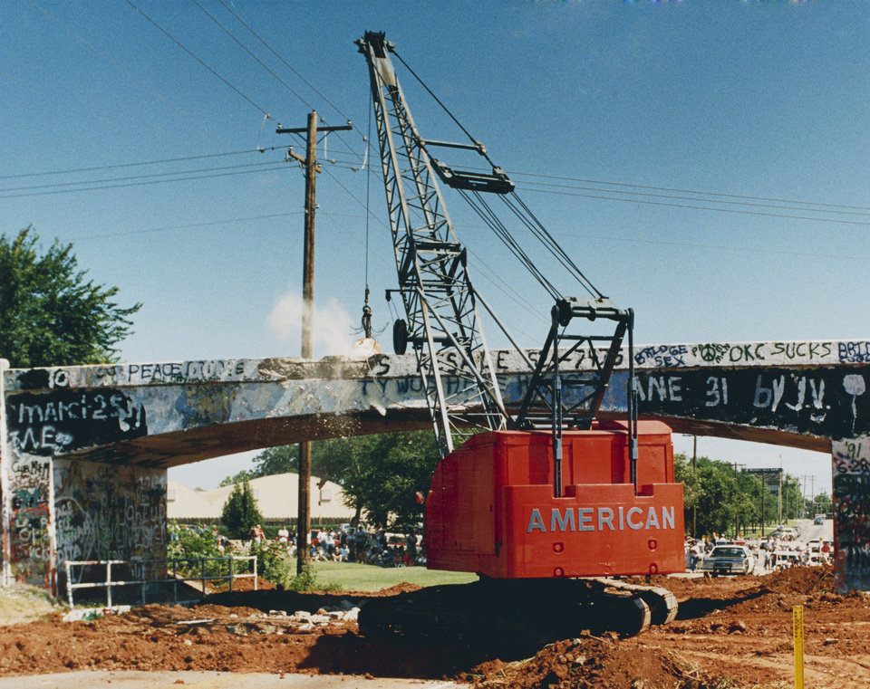 Photo -  Tumbling Down - The wrecking ball drops on the Graffiti Bridge at NW 59 and Western in Oklahoma City.  The landmark site adorned with writings of all types was torn down Saturday.  Staff photo by Steve Gooch.  Photo dated 06/28/1991 and published on 06/30/1991 in The Daily Oklahoman.