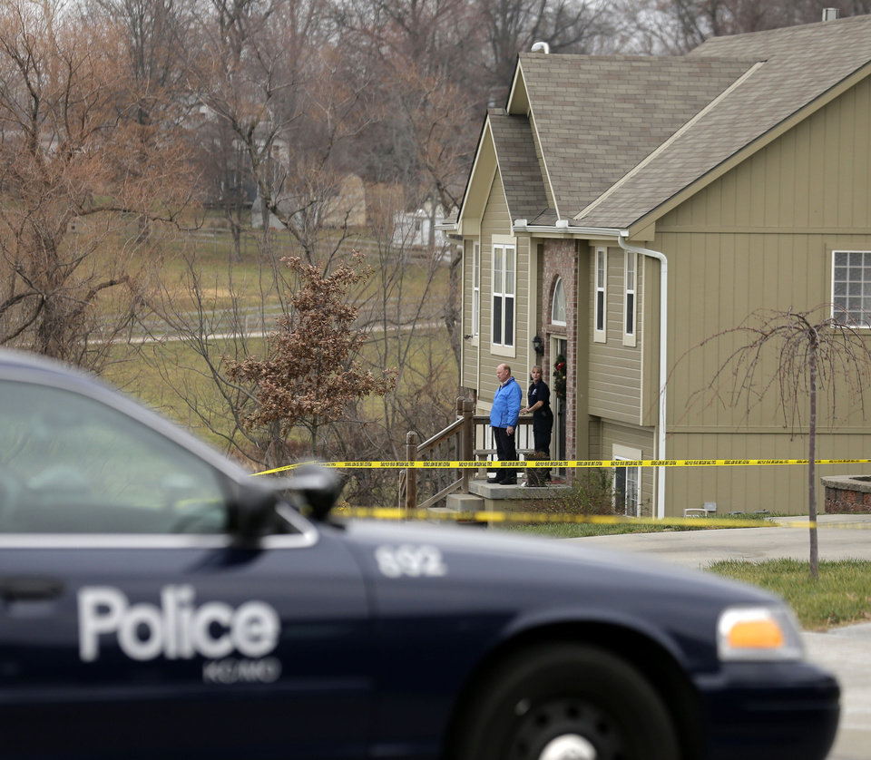 Photo - Investigators stand outside an Independence, Mo., house where police say Kansas City Chiefs linebacker Jovan Belcher fatally shot his girlfriend before driving to the NFL football team's training facility and shooting himself, Saturday, Dec. 1, 2012. (AP Photo/Charlie Riedel)