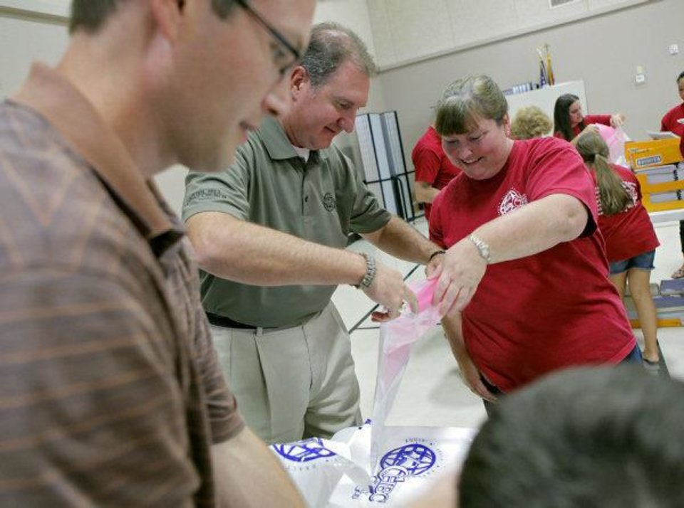 Photo - The Rev. Mark DeMoss, senior pastor of Capitol Hill Baptist Church, center, and church members Jeremy Vogler (left) and Michelle Lessley (right) fill bags with school supplies in preparation for the church's carnival and school supply give-away.  JOHN CLANTON - John Clanton