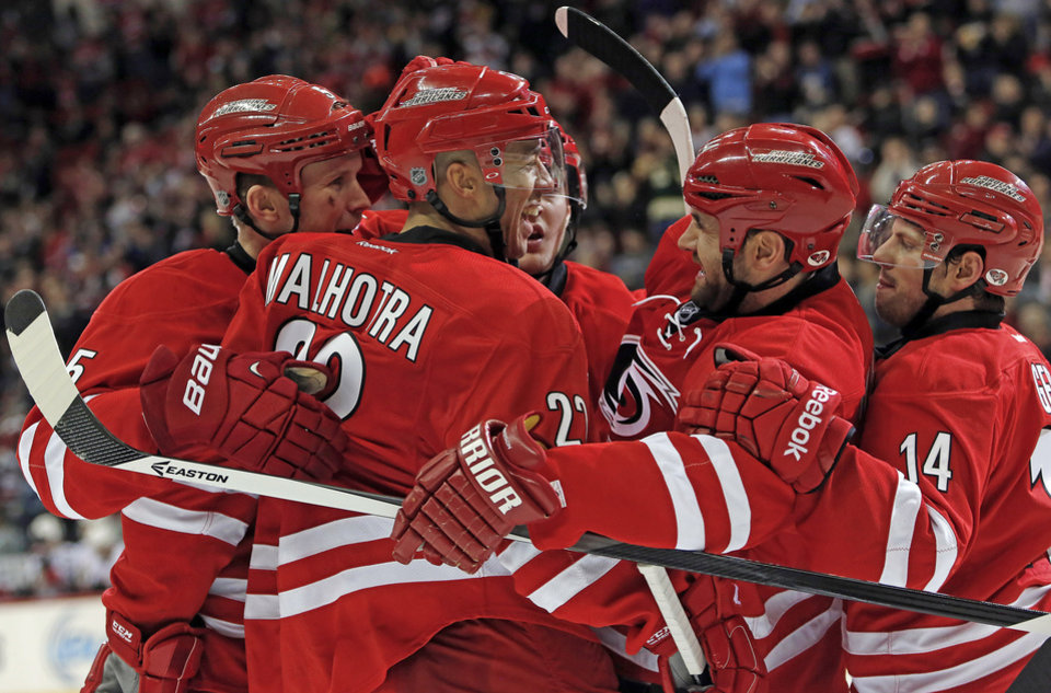 Photo - Carolina Hurricanes' Manny Malhotra (22) is congratulated by teammates after scoring in the second period of an NHL hockey game against the Ottawa Senators in Raleigh, N.C., Saturday, Jan. 25, 2014. Hurricanes won 6-3. (AP Photo/Karl B DeBlaker)