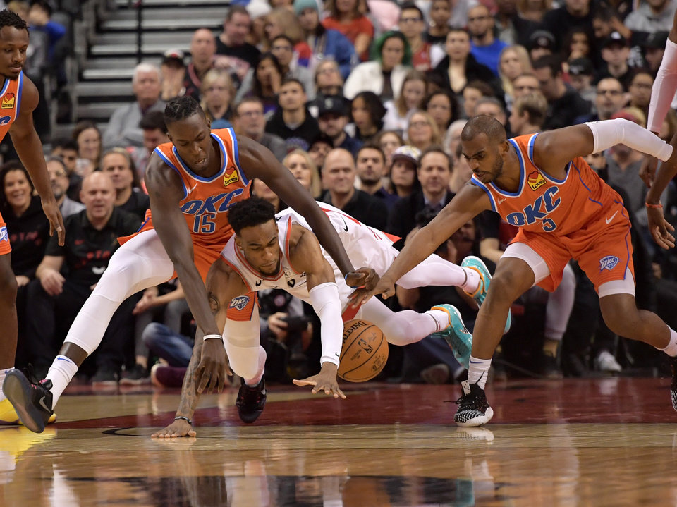 Photo - Dec 29, 2019; Toronto, Ontario, CAN; Toronto Raptors forward Oshae Brissett dives for a loose ball between Oklahoma City Thunder forward Kevin Hervey (15) and guard Chris Paul (3) in the first half at Scotiabank Arena. Mandatory Credit: Dan Hamilton-USA TODAY Sports