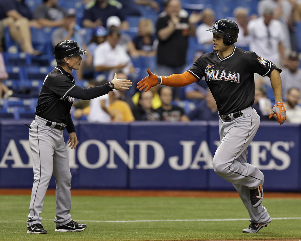 Photo - Miami Marlins' Giancarlo Stanton, right, reaches out to shake hands with third base coach Brett Butler after his two-run home run off Tampa Bay Rays relief pitcher Brad Boxberger during the seventh inning of an interleague baseball game Thursday, June 5, 2014, in St. Petersburg, Fla. Marlins' Donovan Solano also scored on the hit. (AP Photo/Chris O'Meara)