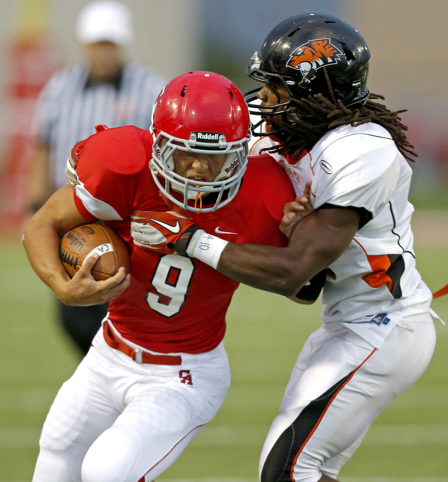 Carl Albert\'s Caleb Toney tries to get past Coweta\'s Jakeem Johnson during a high school football game at Carl Albert in Midwest City, Friday, September 7, 2012. Photo by Bryan Terry, The Oklahoman
