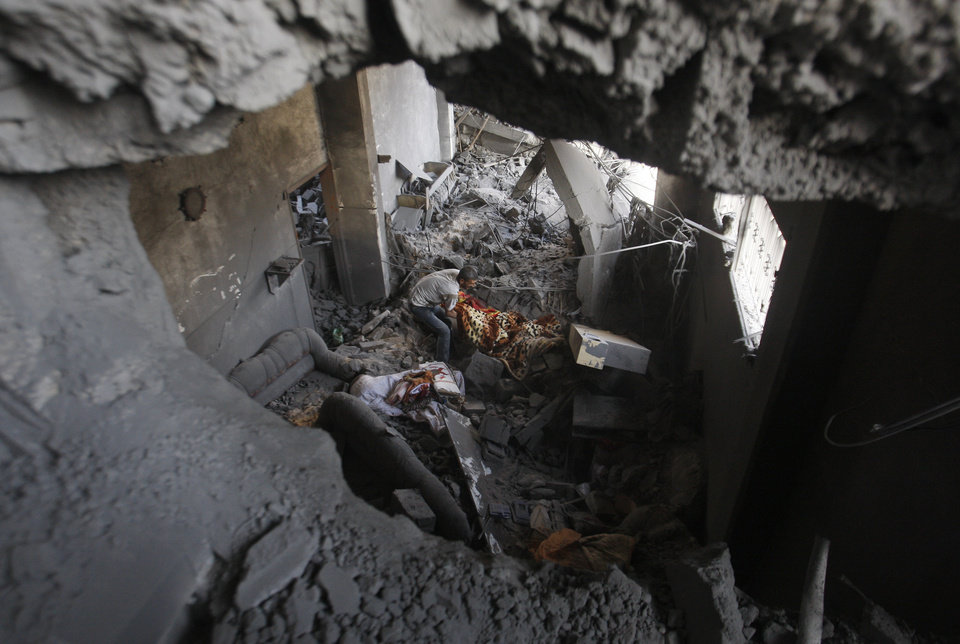 Photo -   Palestinians inspect the rubble in a house destroyed on Sunday by an Israeli strike in Gaza City, Monday, Nov. 19, 2012. The Palestinian civilian death toll mounted Monday as Israeli aircraft struck densely populated areas in the Gaza Strip in its campaign to quell militant rocket fire menacing nearly half of Israel's population. (AP Photo/Hatem Moussa)