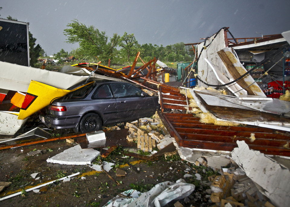Photo - A car sits under debris from the Loves Country Store that was destroyed after a tornado damaged the area around I-40 and Choctaw Road on Monday, May 10, 2010, in Oklahoma City, Okla.  Photo by Chris Landsberger, The Oklahoman
