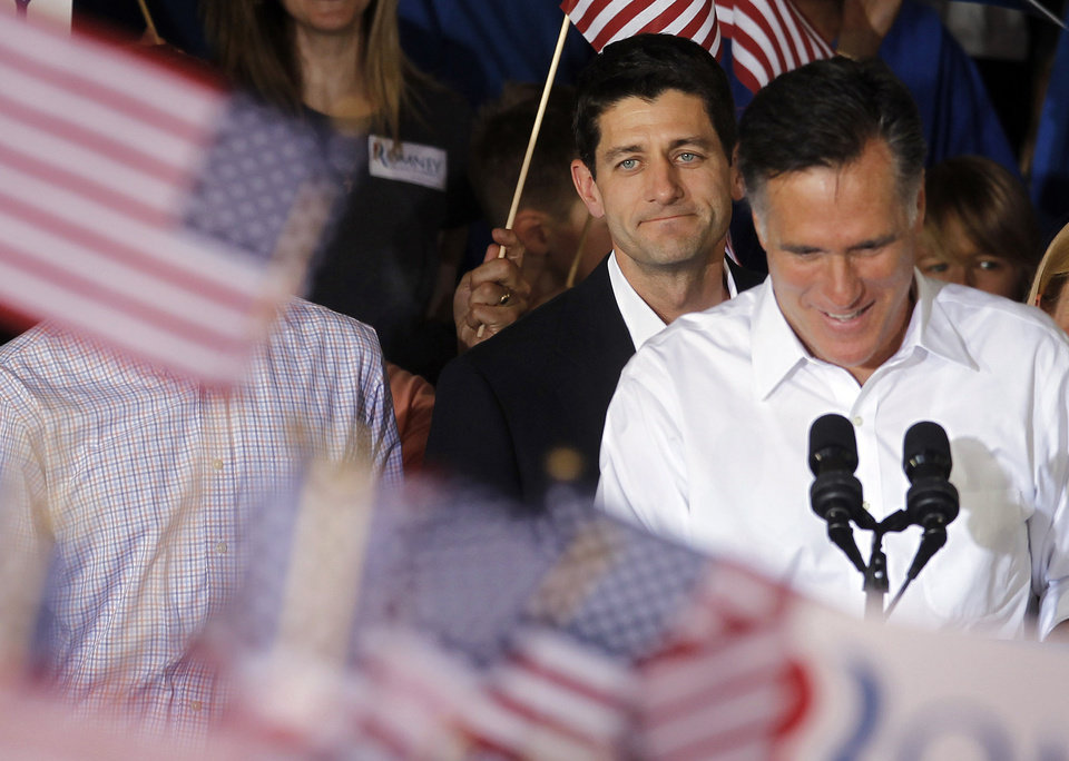 Photo -   Republican presidential candidate, former Massachusetts Gov. Mitt Romney, right, with his newly announced vice presidential running mate, Rep. Paul Ryan, R-Wis., standing behind him, during a campaign rally in Manassas, Va., Saturday, Aug. 11, 2012. (AP Photo/Pablo Martinez Monsivais)