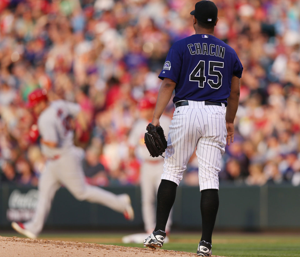 Photo - Colorado Rockies starting pitcher Jhoulys Chacin, front, looks on as St. Louis Cardinals' Matt Adams, back, circles the bases after hitting a solo home run in the fifth inning of a baseball game in Denver on Monday, June 23, 2014. (AP Photo/David Zalubowski)