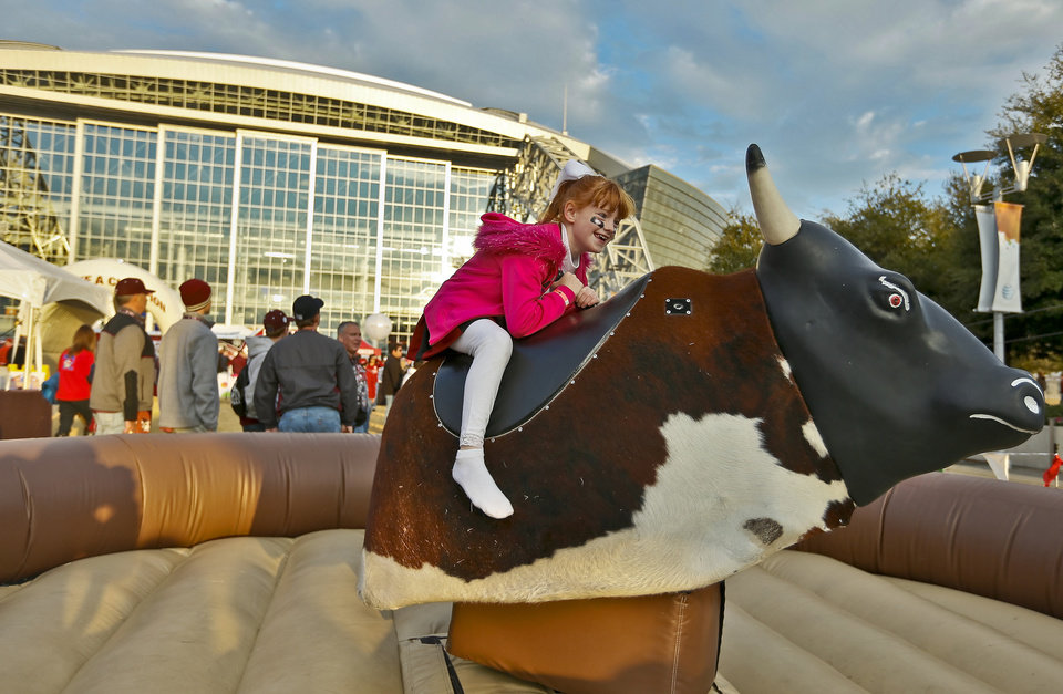 Photo - Lauren Knight, of Norman, hangs on tight while riding the mechanical bull during the college football Cotton Bowl game between the University of Oklahoma Sooners (OU) and Texas A&M University Aggies (TXAM) at Cowboy's Stadium on Friday Jan. 4, 2013, in Arlington, Tx. Photo by Chris Landsberger, The Oklahoman