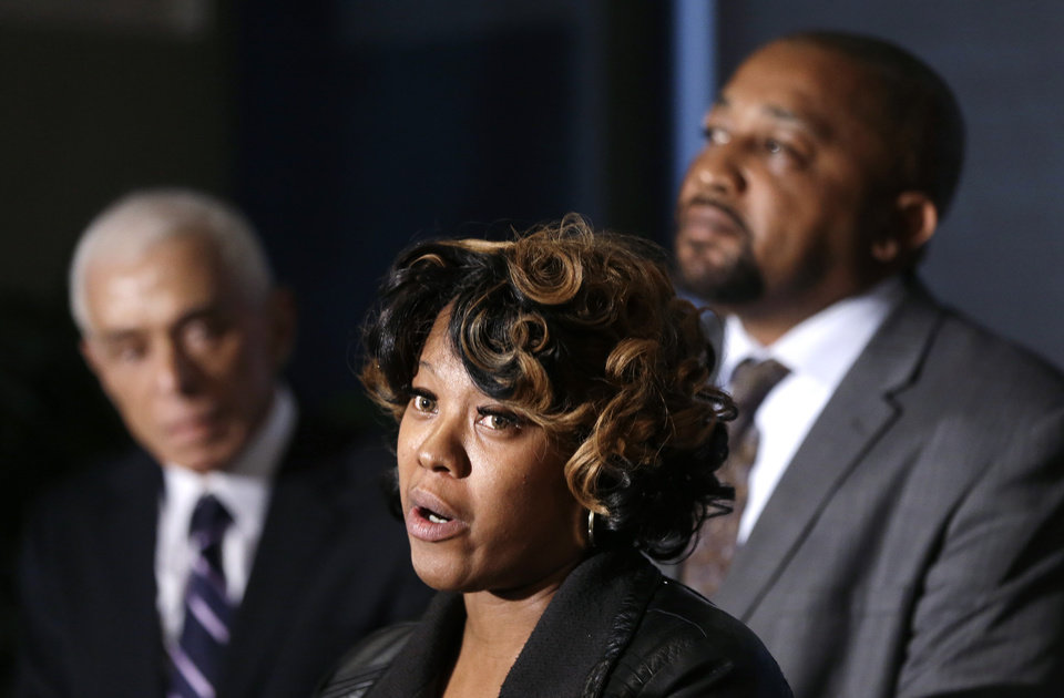 Photo - Monica McBride, center, and Walter Ray Simmons, right, the parents of Renisha McBride address the media with attorney Gerald Thurswell, left, during a news conference in Southfield, Mich., Friday, Nov. 15, 2013. Their daughter was shot on Nov. 2  in the face on Theodore P. Wafer's front porch in Dearborn Heights. (AP Photo/Carlos Osorio)