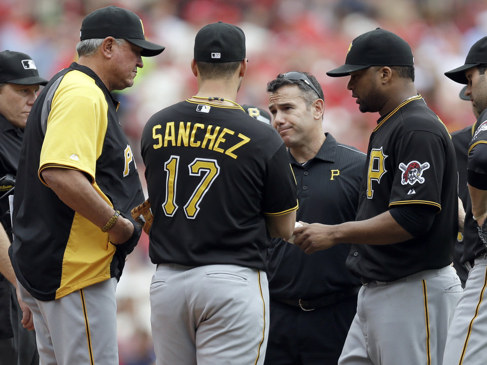 Photo - Pittsburgh Pirates starting pitcher Francisco Liriano, right, hands the ball to manager Clint Hurdle, left, as he leaves the baseball game during the third inning against the St. Louis Cardinals on Saturday, April 26, 2014, in St. Louis. (AP Photo/Jeff Roberson)