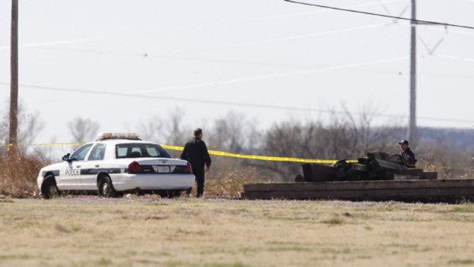 Photo - Investigators work on a crime scene in the death of Rosalin Reynolds, 8, on Wednesday in a field behind the Watonga apartment complex where she lived.  Steve Gooch - The Oklahoman