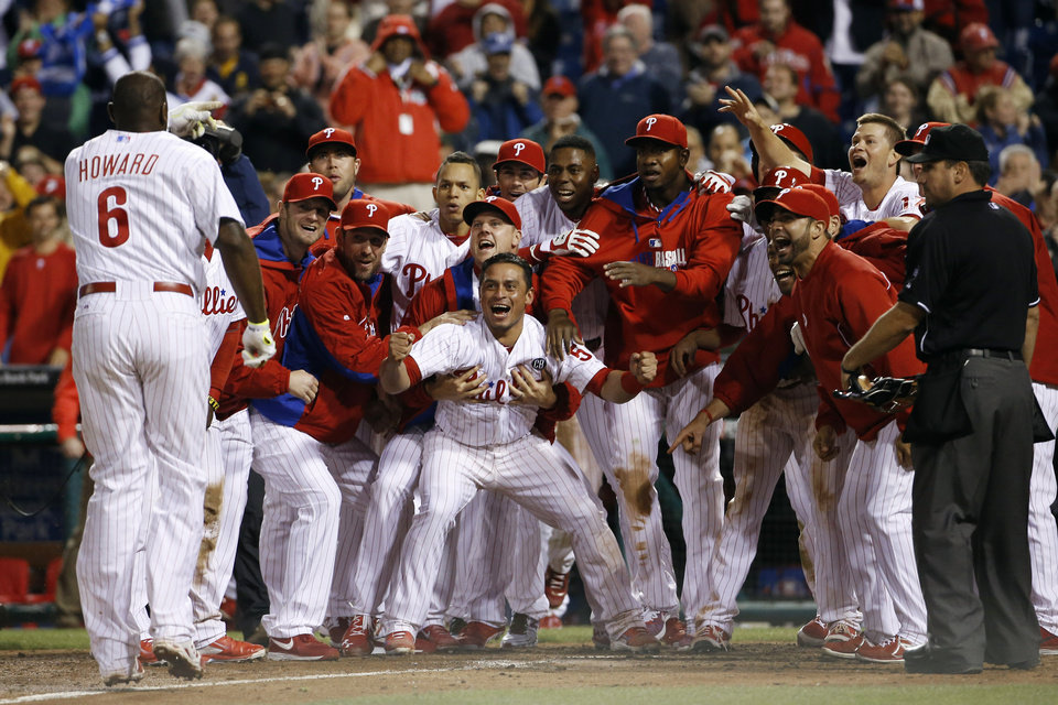 Photo - Philadelphia Phillies players celebrate and wait for Ryan Howard, left, to cross home plate after Howard's game-winning three-run home run off Colorado Rockies relief pitcher Boone Logan during the ninth inning of a baseball game, Wednesday, May 28, 2014, in Philadelphia. Philadelphia won 6-3. (AP Photo/Matt Slocum)
