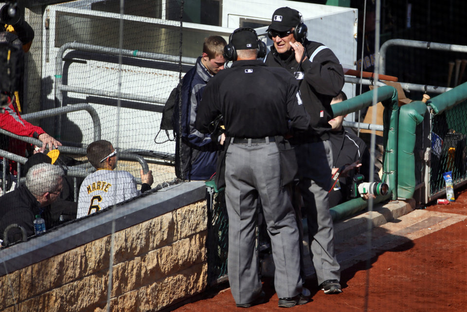 Photo - First base umpire Bob Davidson, right, and home plate umpire John Hirschbeck, center, talk over headsets as a pickoff safe call at first base is reviewed in the tenth inning of an opening day baseball game against the Chicago Cubs on Monday, March 31, 2014, in Pittsburgh. The safe call was overturned and Cubs' Emilio Bonifacio was ruled out. The Pirates won 1-0 in ten innings. (AP Photo/Gene J. Puskar)