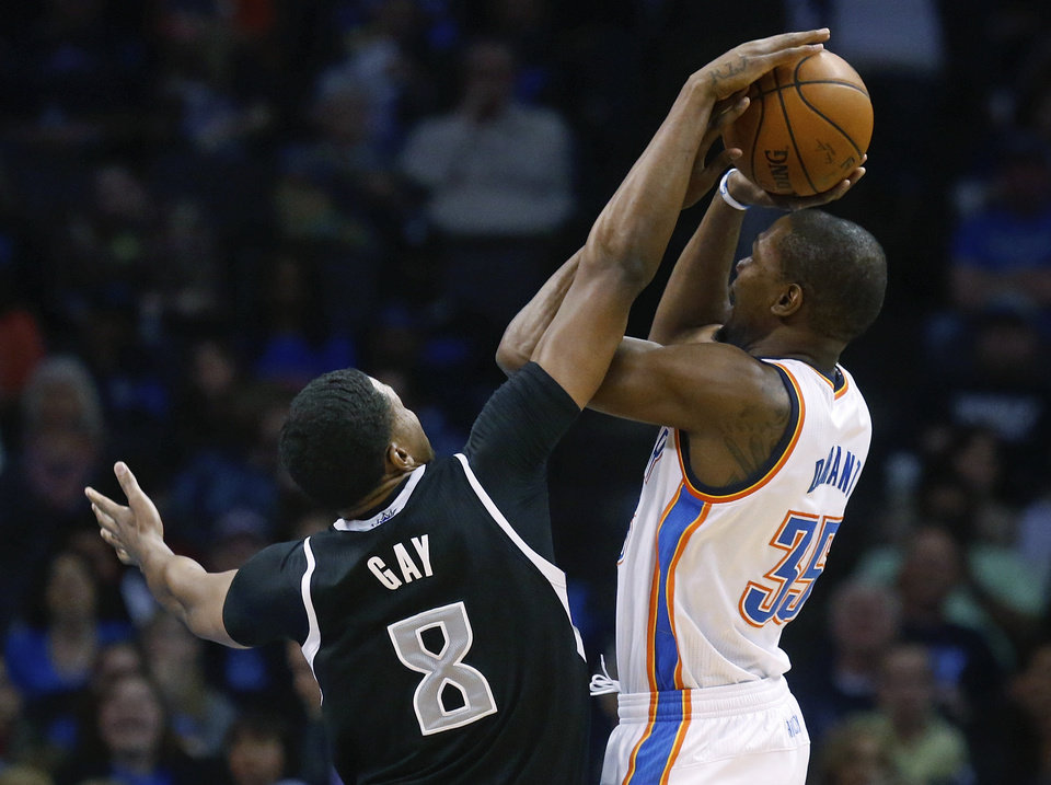 Photo - Oklahoma City Thunder forward Kevin Durant (35) is fouled by Sacramento Kings forward Rudy Gay (8) duringthe first quarter of an NBA basketball game in Oklahoma City, Friday, March 28, 2014. (AP Photo/Sue Ogrocki)