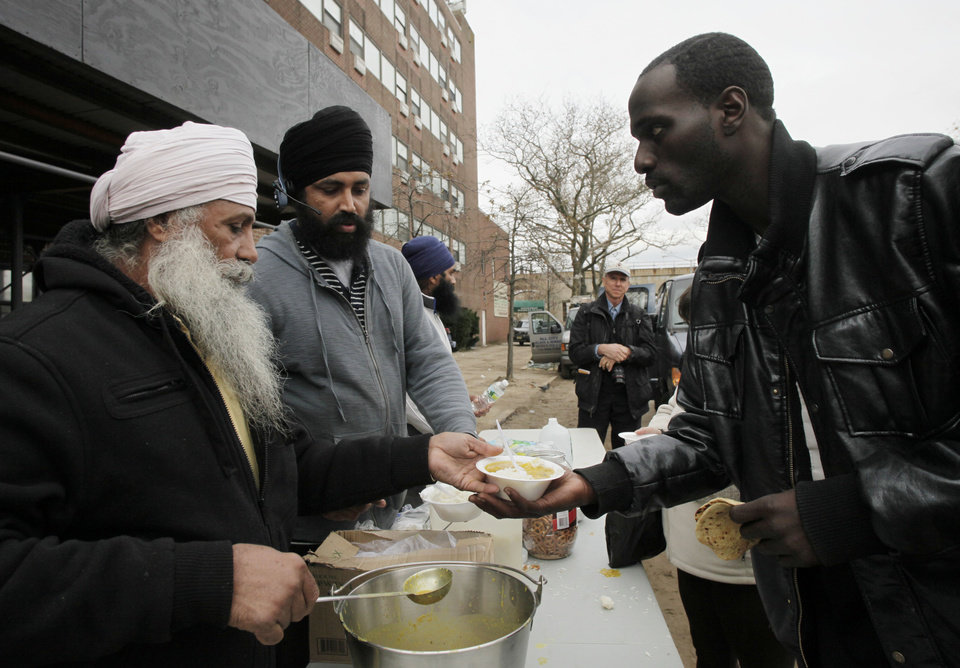 Photo - Singh Tarlok, left, hands a bowl of hot food to Arnell Franklin at a food line run by community volunteers in the oceanside community of Far Rockaway in the Queens borough of New York on Thursday, Nov. 1, 2012. The area was devastated by superstorm Sandy. (AP Photo/Mark Lennihan) ORG XMIT: NYML136