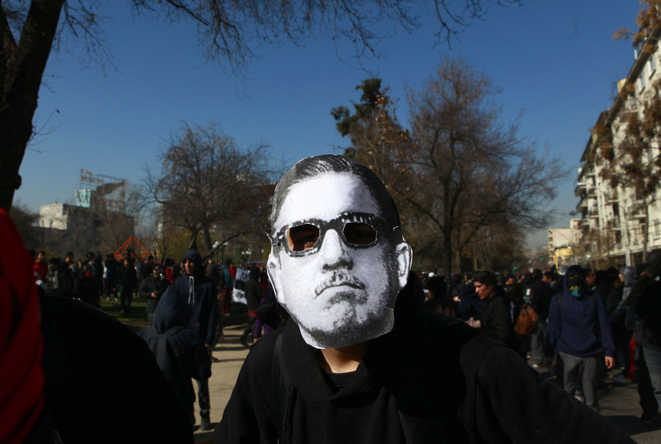 Photo -   A demonstrator wears a mask depicting late Chilean dictator Gen. Augusto Pinochet during a student march to demand free education in Santiago, Chile, Wednesday, Aug. 8, 2012. Police used water cannons and tear gas to break up the protest and three buses were set ablaze. (AP Photo / Luis Hidalgo)