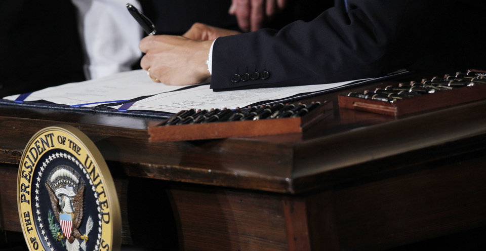 Twenty-two pens are shown next to President Barack Obama as he signs the health care reform bill March 23, 2010, in the East Room of the White House in Washington.  \AP Archives Photo