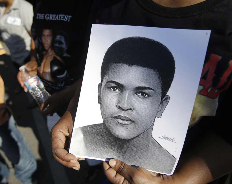 Photo - A mourner holds a photo of Muhammad Ali, as she waits for the procession to pass with the hearse carrying the body of Muhammad Ali, Friday, June 10, 2016, in Louisville, Ky. (AP Photo/Darron Cummings)