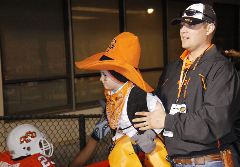 Photo - Jon Pace holds his son Wyatt Pace, 4, as he high fives Cowboy players as they come on the field before the college football game between the University of Oklahoma Sooners (OU) and Oklahoma State University Cowboys (OSU) at Boone Pickens Stadium on Saturday, Nov. 29, 2008, in Stillwater, Okla. STAFF PHOTO BY DOUG HOKE