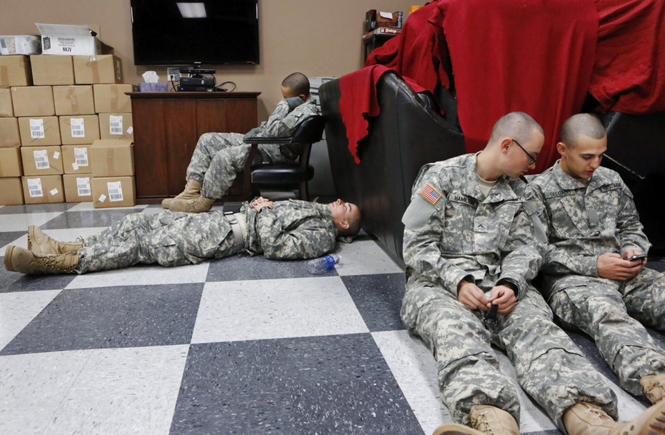 After eating, soldiers found different ways to spend their time waiting for their flights to arrive.  Several took naps and others made phone calls. Some listened to music through their headphones  or played games on their cell phones. Others sat in small groups to talk. In another room, troops watched movies on a large projection screen. Nearly 700 soldiers from Ft. Sill, most of whom had recently completed their basic training,  arrived at Will Rogers World Airport on buses in pre-dawn hours Thursday,  Dec. 20, 2012, to catch flights to join join their families for the Christmas holidays.  The troops were welcomed by Blue Star Mothers and other volunteers at the YMCA Military Welcome Center, where they were offered pizzas, doughnuts,  chips, sub sandwiches, desserts, hot coffee and cold beverages. Local merchants donated 250 pizzas, 60 dozen doughnuts and the submarine sandwiches.   Photo by Jim Beckel, The Oklahoman