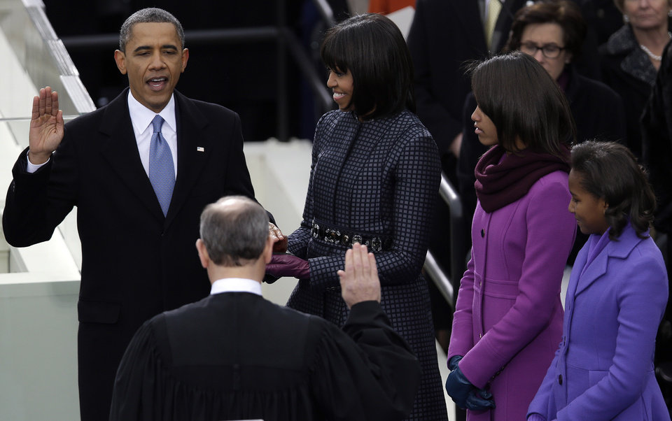Photo - President Barack Obama takes the oath of office from Chief Justice John Roberts at the ceremonial swearing-in at the U.S. Capitol during the 57th Presidential Inauguration in Washington, Monday, Jan. 21, 2013 as first lady Michelle Obama and his daughters Malia and Sasha look on. (AP Photo/Evan Vucci)
