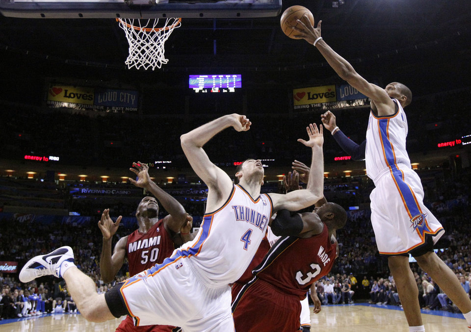 Photo - Oklahoma City's Russell Westbrook (0) shoots a lay up as Oklahoma City's Nick Collison (4) Miami's Joel Anthony (50) and Miami's Dwyane Wade (3) position for a rebound during the NBA basketball game between Oklahoma City and Miami at the OKC Arena in Oklahoma City, Thursday, Jan. 30, 2011. Photo by Sarah Phipps, The Oklahoman