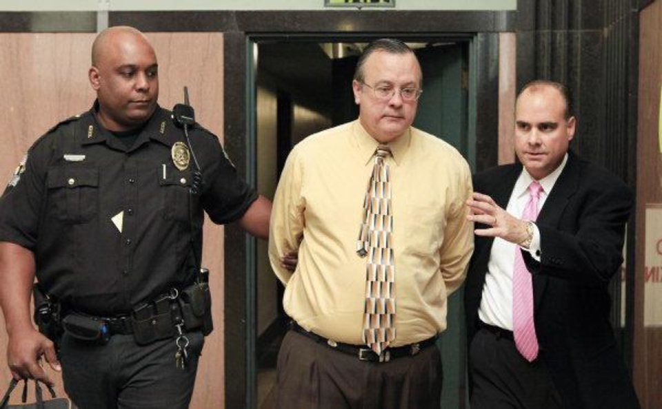 Photo - As he turned himself in on Nov. 15, 2010 , Roger Q. Melson Jr., a former auditor for the Commissioners of the Land Office, is flanked by Deputy Sheriff Jawan Thomas, left and Melson's attorney, Billy Bock.  PAUL B. SOUTHERLAND