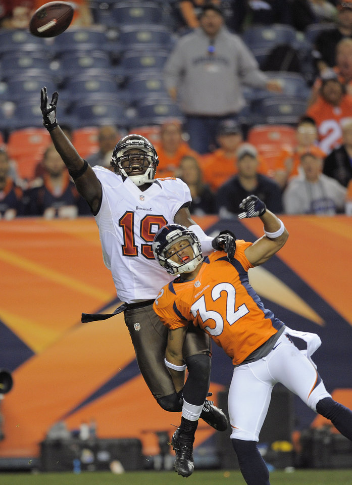 Photo - Tampa Bay Buccaneers wide receiver Mike Williams (19) leaps unsuccessfully for a pass over Denver Broncos defensive back Tony Carter (32) in the fourth quarter of an NFL football game, Sunday, Dec. 2, 2012, in Denver. Denver won 31-23 and clinched the AFC West division. (AP Photo/Jack Dempsey)