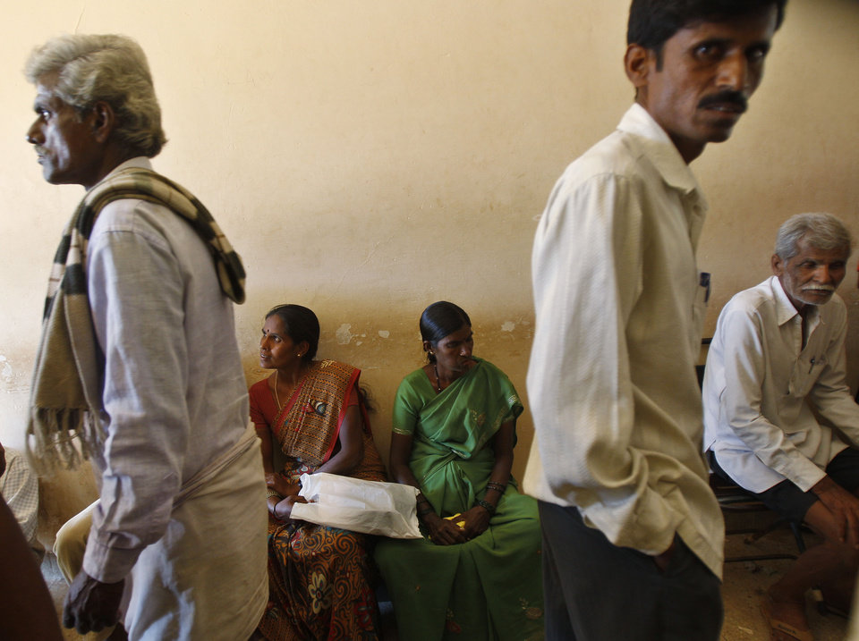 Photo - In this Dec.10, 2012 photo, people wait to get their land registered at the government registrar's office in Hoskote 30 kilometers (19 miles) from Bangalore in the southern Indian state of Karnataka. For years, Karnataka's land records were a quagmire of disputed, forged documents maintained by thousands of tyrannical bureaucrats who demanded bribes to do their jobs. In 2002, there were hopes that this was about to change. (AP Photo/Aijaz Rahi)