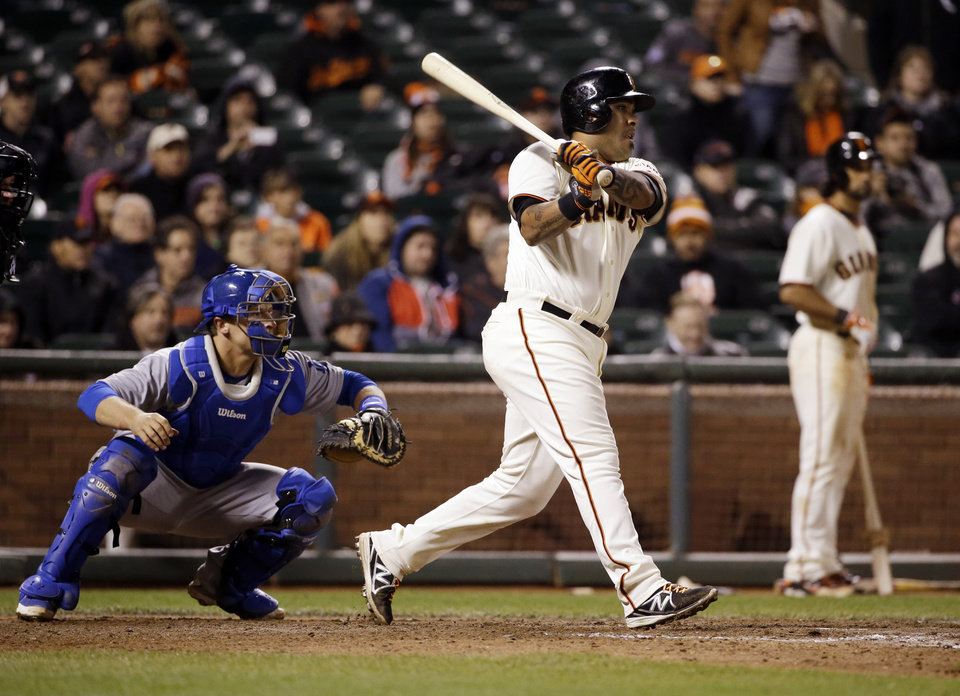 Photo - San Francisco Giants' Hector Sanchez singles in the game-winning run during the 12th inning of a baseball game against the Los Angeles Dodgers on Wednesday, April 16, 2014, in San Francisco. San Francisco won 3-2.  (AP Photo/Marcio Jose Sanchez)
